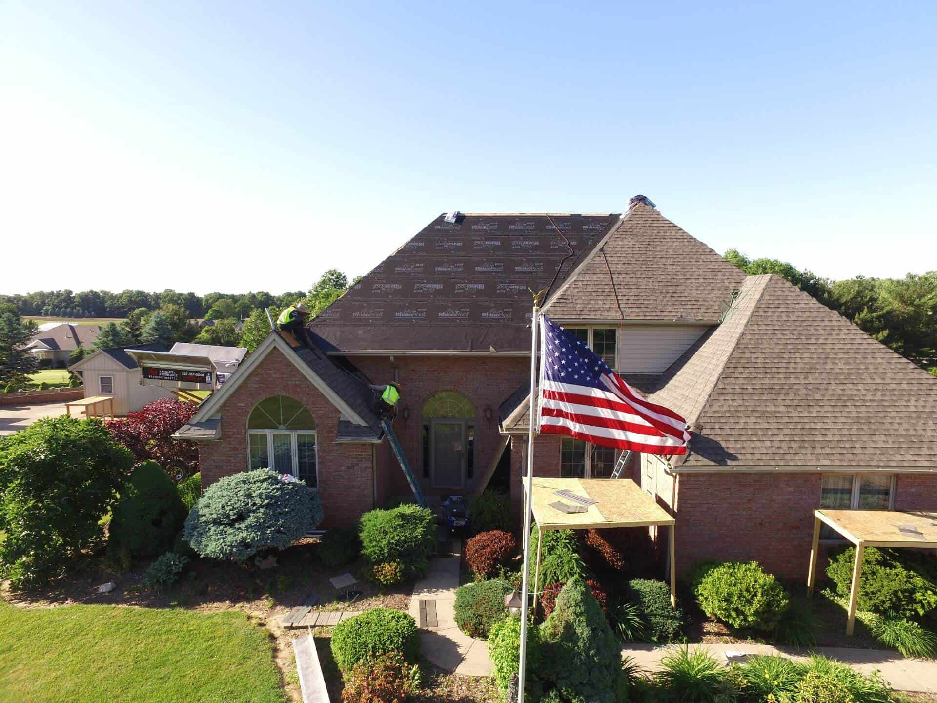 roofing contractor is on a large house doing a roof replacement with American flag flying in front