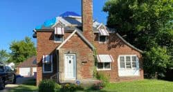 Mansfield Roofing brick masonry home with emergency tarps on roof and it needs a new roof installation