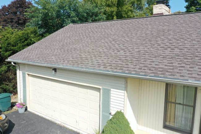 roofers in Mansfield Ohio roofing project home with new shingle roof and white vinyl siding