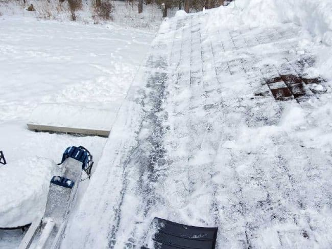 roofers ladder to remove snow and ice because of ice dams