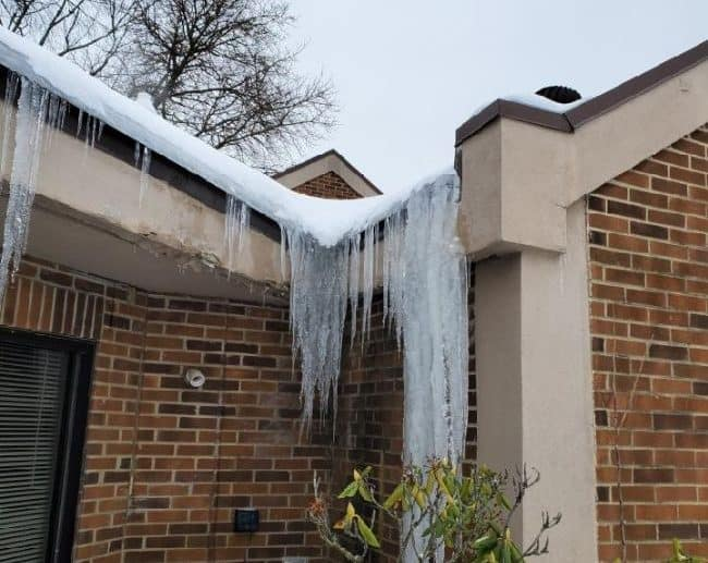 home with icicles hanging on edge because of ice dams