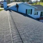 roofer on a shingle roof during a roof replacement