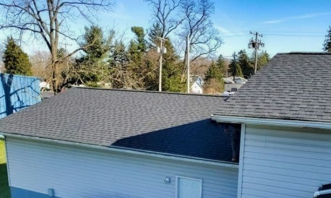 roofing companies near me installing new gray shingle roof on home